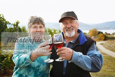 Couple in Vineyard, Raising Glasses of Wine