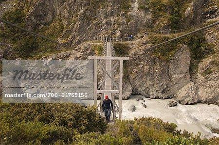 Man Crossing Bridge over River, Hooker Valley, Canterbury, New Zealand