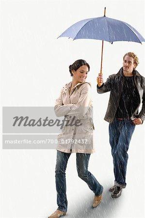 man holding umbrella over woman in the rain stock photo