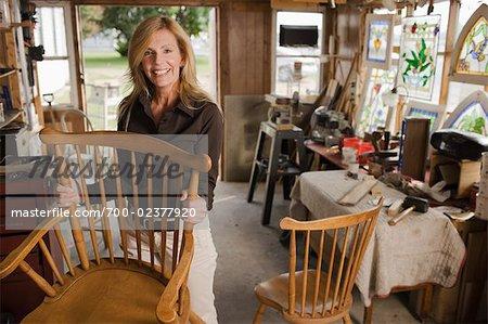 Woman Repairing Furniture In Workshop   Stock Photo