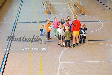 Children Playing Soccer in School Gym
