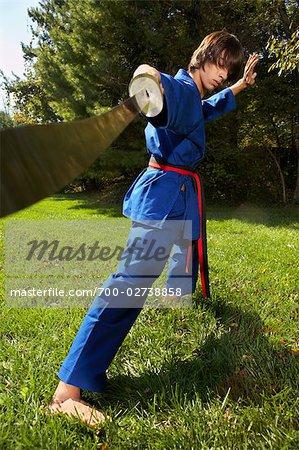 Teenage Boy in Karate Uniform Holding Sword - Stock Photo