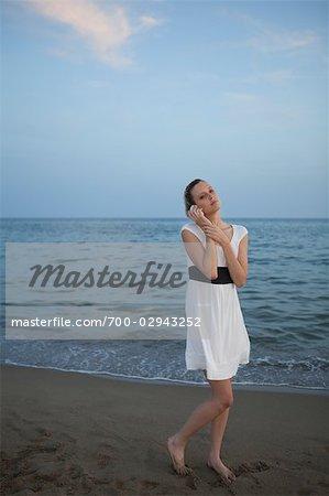 Woman on Beach Listening to Seashell