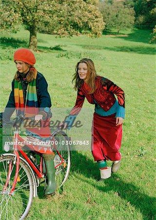Mother pushing Daughter on Bicycle