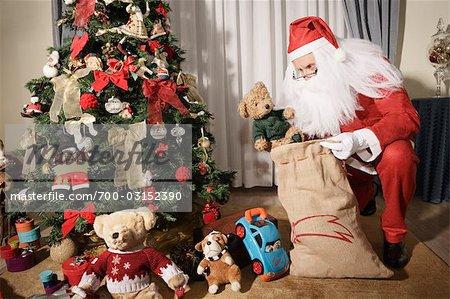 santa claus putting presents under christmas tree stock photo - Santa Claus Presents