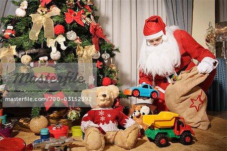 santa claus putting presents under christmas tree stock photo - Santa Claus With Presents