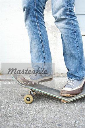 Teenager Standing on Broken Skateboard