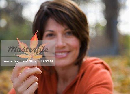 Portrait of Woman Holding Autumn Leaf
