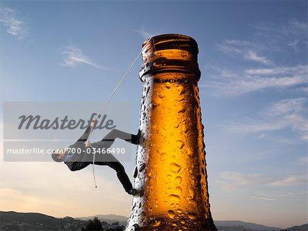 Businessman Climbing up Beer Bottle
