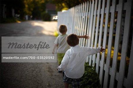 Boys Walking Beside White Picket Fence, Sauble Beach, Ontario, Canada