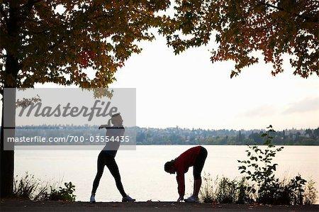 Silhouette of Runners Stretching, Green Lake Park, Seattle, Washington, USA