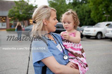 Nurse holding Child Outdoors