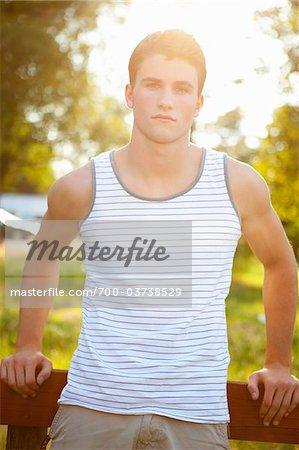Teenage Boy Leaning Against Fence