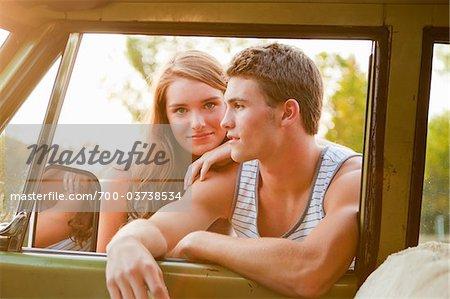 Teenage Couple Leaning Through Car Window