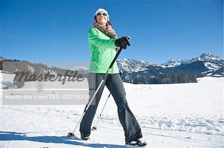 Woman Walking with Ski Poles in Winter