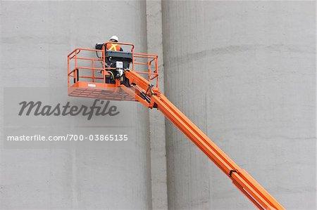 Worker on Crane Inspecting Silo