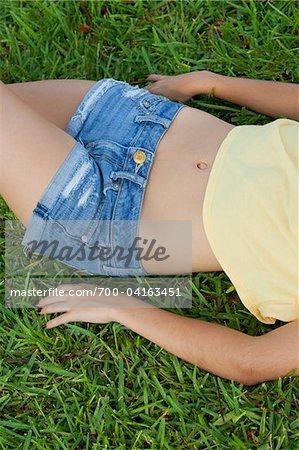 Teenage Girl with Bare Midriff Lying on Grass