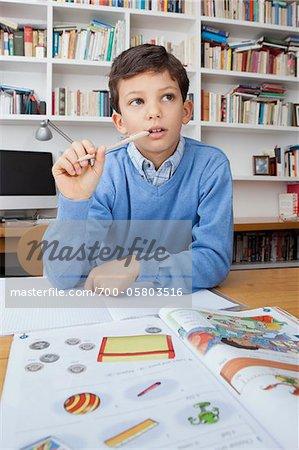 Boy Thinking While Doing Homework