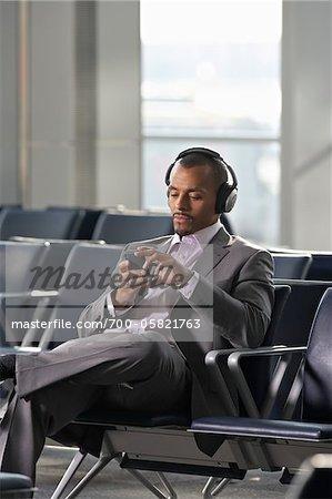 Businessman Wearing Headphones in Waiting Area of Airport