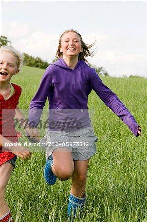 Two Girls Running in Field