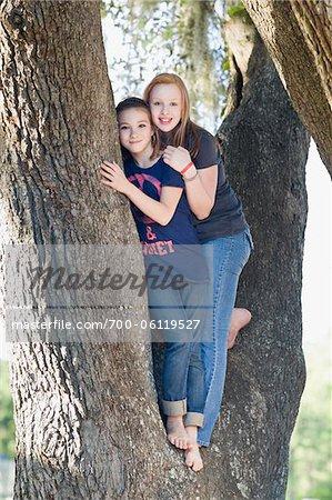 Two Teenage Girls Hugging in Tree