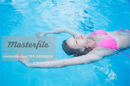 Teenage Girl Floating in Swimming Pool