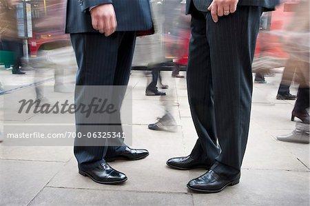 Two Businessmen Standing Amongst Pedestrian Traffic