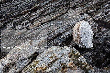Light-Colored Rocks on Dark Striated Rocky Terrain