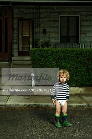 Boy Standing on Neighbourhood Street in Diaper and Rubber Boots