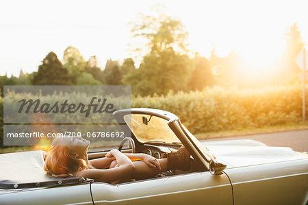 Teenage girl laying back in a 1966 Triumph in Portland Oregon.