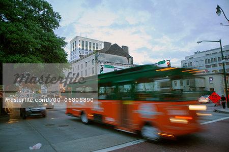 Tour bus cruising down bay street at dusk.Savannah, georgia.