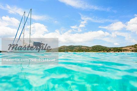Close-up of ocean and sailboat at Rondinara Beach, (between Bonifacio and Porto-Vecchio) Corsica, France