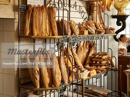 Fresh bread and baguettes on display rack in bakery, Le Boulanger des Invalides, Paris, France