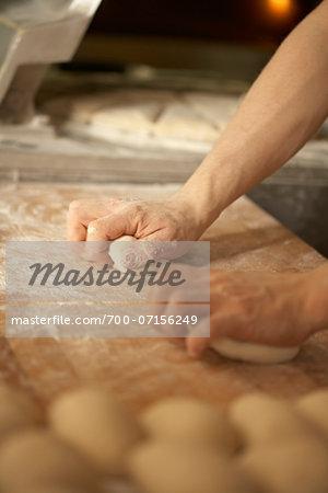 Close-up of male baker's hands kneading bread dough on floured board, Le Boulanger des Invalides, Paris, France