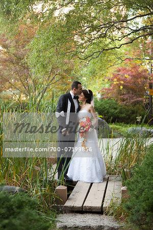 Portrait of groom kissing bride outdoors, standing in public garden, Ontario, Canada