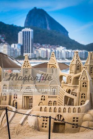 Close-up of sand sculpture with buildings along shoreline in background, Copacabana Beach, Rio de Janeiro, Brazil