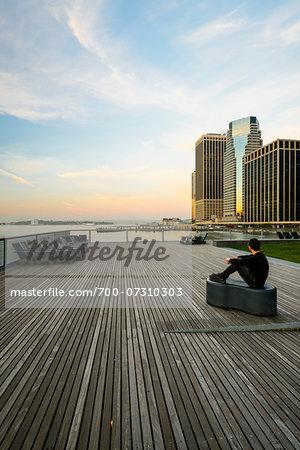 Man sitting on Pier 16, looking at view toward downdown skyline, Lower Manhattan, Manhattan, New York City, New York, USA