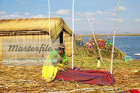 Woman in Peruvian clothing displaying traditional art outdoors, Floating Island of Uros, Lake Titicaca, Peru