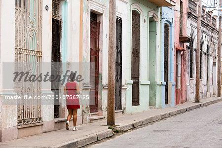 Woman waling on sidewalk, street scene with row of colorful houses, Camaguey, Cuba