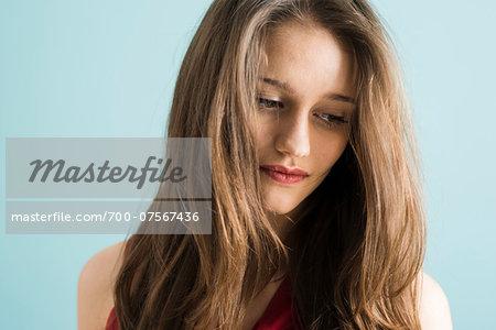 Close-up portrait of teenage girl looking downwards, studio shot on blue background