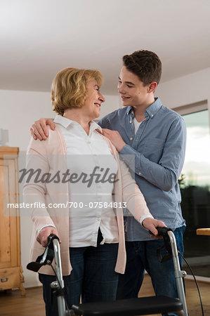 Teenage boy helping Grandmother use walker at home, Germany