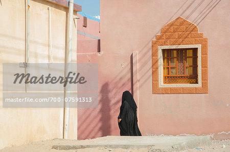 Muslim Woman in Burqua and Hijab Walking passed Typical Omani House Window, Al Ashkharah, Oman