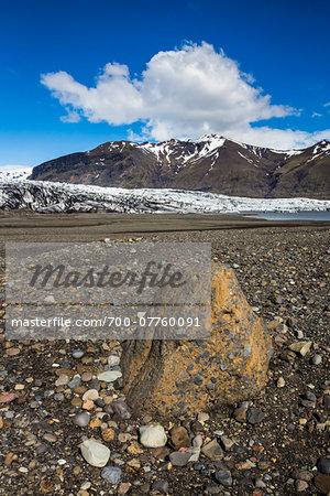Close-up of boulder and rocks with glacier and mountains in background, Skaftafellsjokull, Skaftafell National Park, Iceland