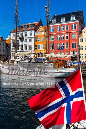 Boats on waterfront with Norwegian flag, Nyhavn Harbour, Copenhagen, Denmark