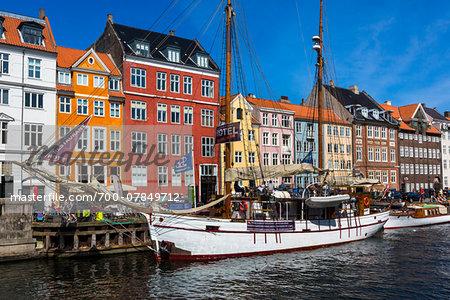 Historical, wooden sailing ship docked at waterfront, Nyhavn Harbour, Copenhagen, Denmark