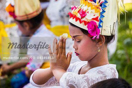 Close-up og Legong dancer praying at a temple festival, Gianyar, Bali, Indonesia
