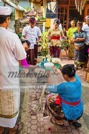 Woman holdng religious offering at Balinese wedding, Petulu Village near Ubud, Bali, Indonesia