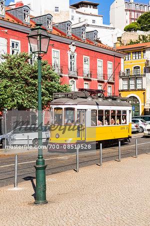 Old yellow tram arriving at Largo das Portas do Sol, Alfama District, Lisbon, Portugal