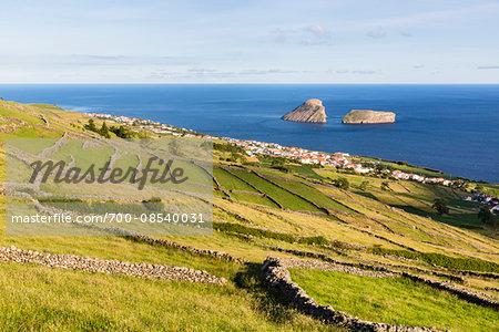Agricultural land with lava stone walls in front of the view to the Ilheus das Cabras, Serra da Ribeirinha, Terceira Island, Azores, Portugal