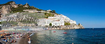 Tourists enjoying the beach at the mountain side town of Amalfi, Amalfi Coast, Italy